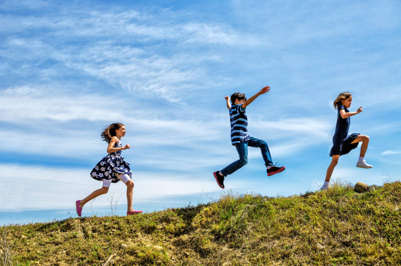 Children skipping and jumping up a hill.