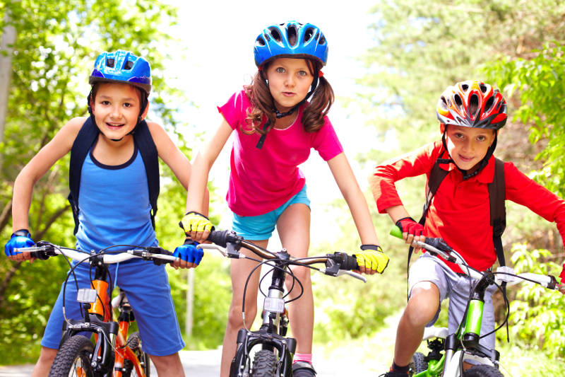 Three little cyclists riding their bikes