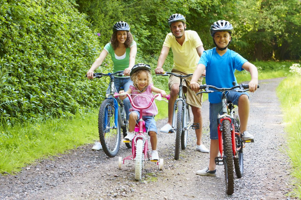 Active young mixed race family enjoying bike ride in the countryside