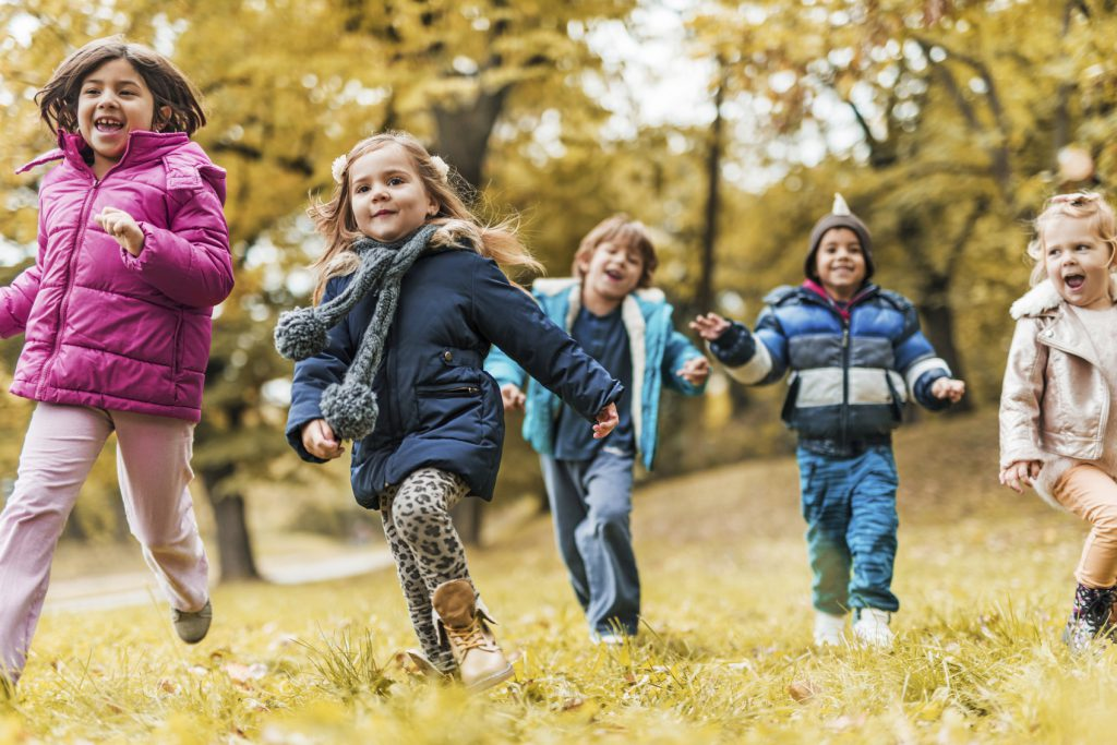 Group of cheerful children running in the park and having fun in autumn.