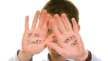 A man holding up his hands with If in doubt, speak out written on them